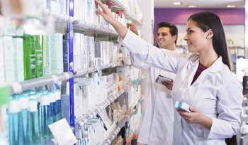 Happy adult pharmacist and pharmacy technician posing in drugstore
