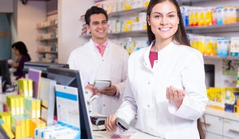 Professional young pharmaceutists at reception of drugstore ready to help